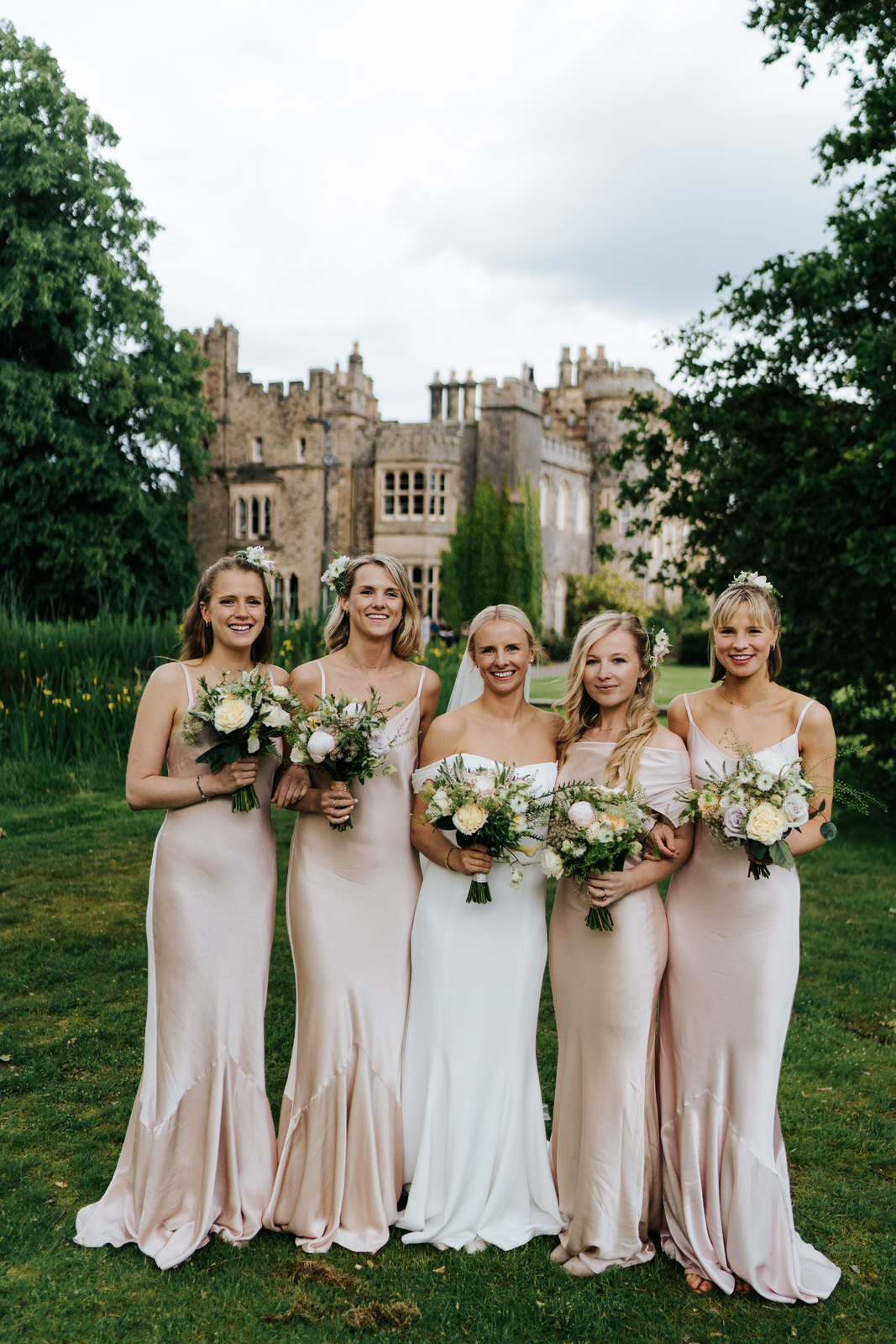 Posed photograph of bridesmaids and bride holding bouquets with Hawarden Castle in the background