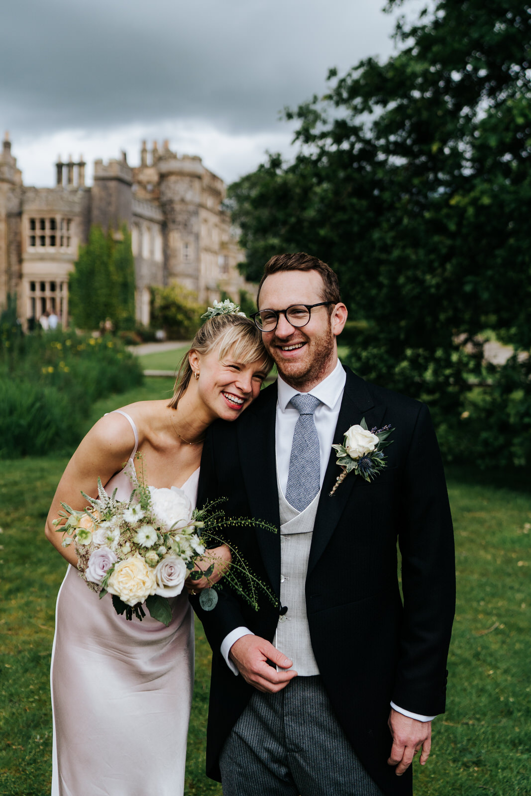 Groom and bride's siter smile during formal photograph with Hawarden Castle in the background