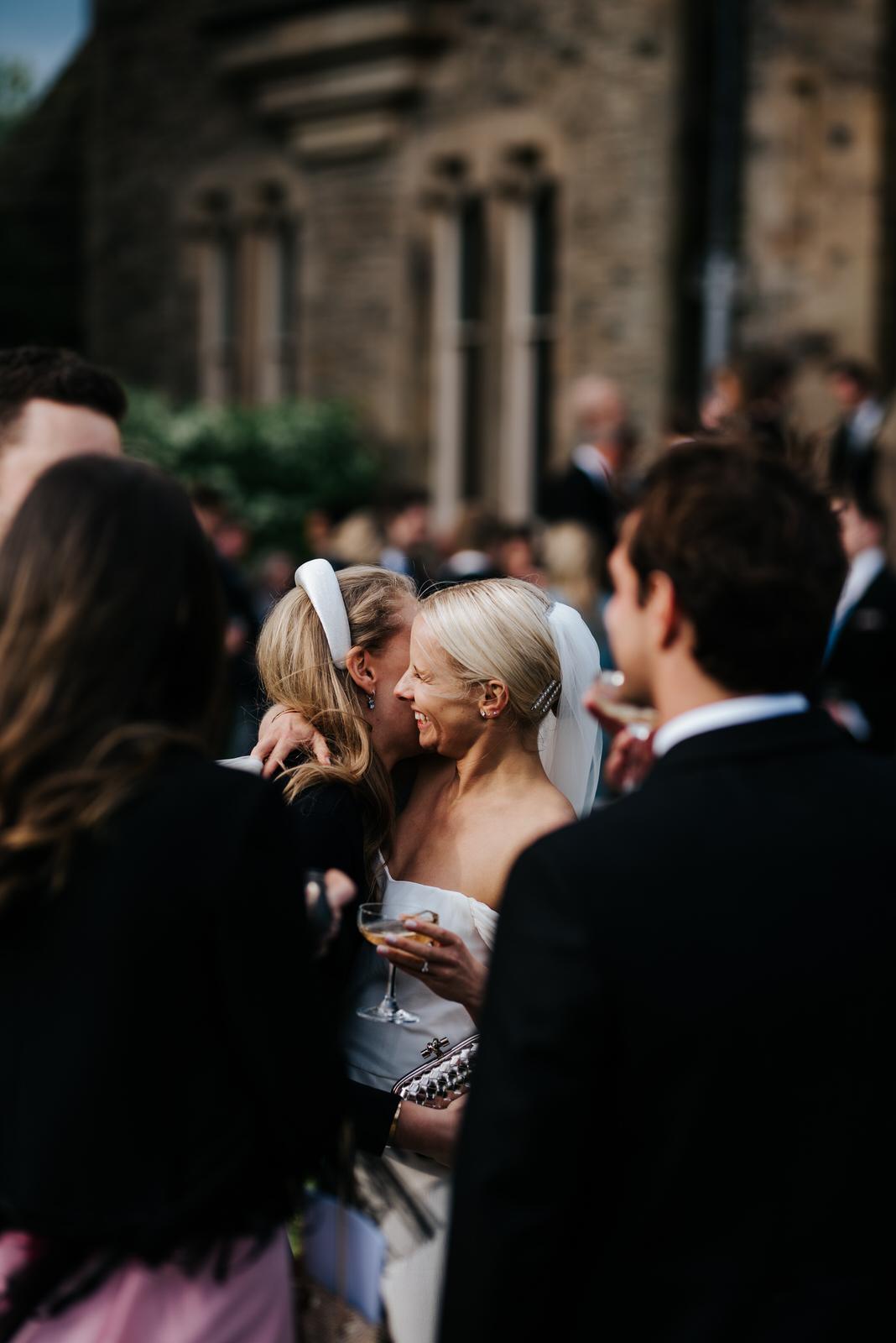 Bride hugs close friend during Champagne Reception