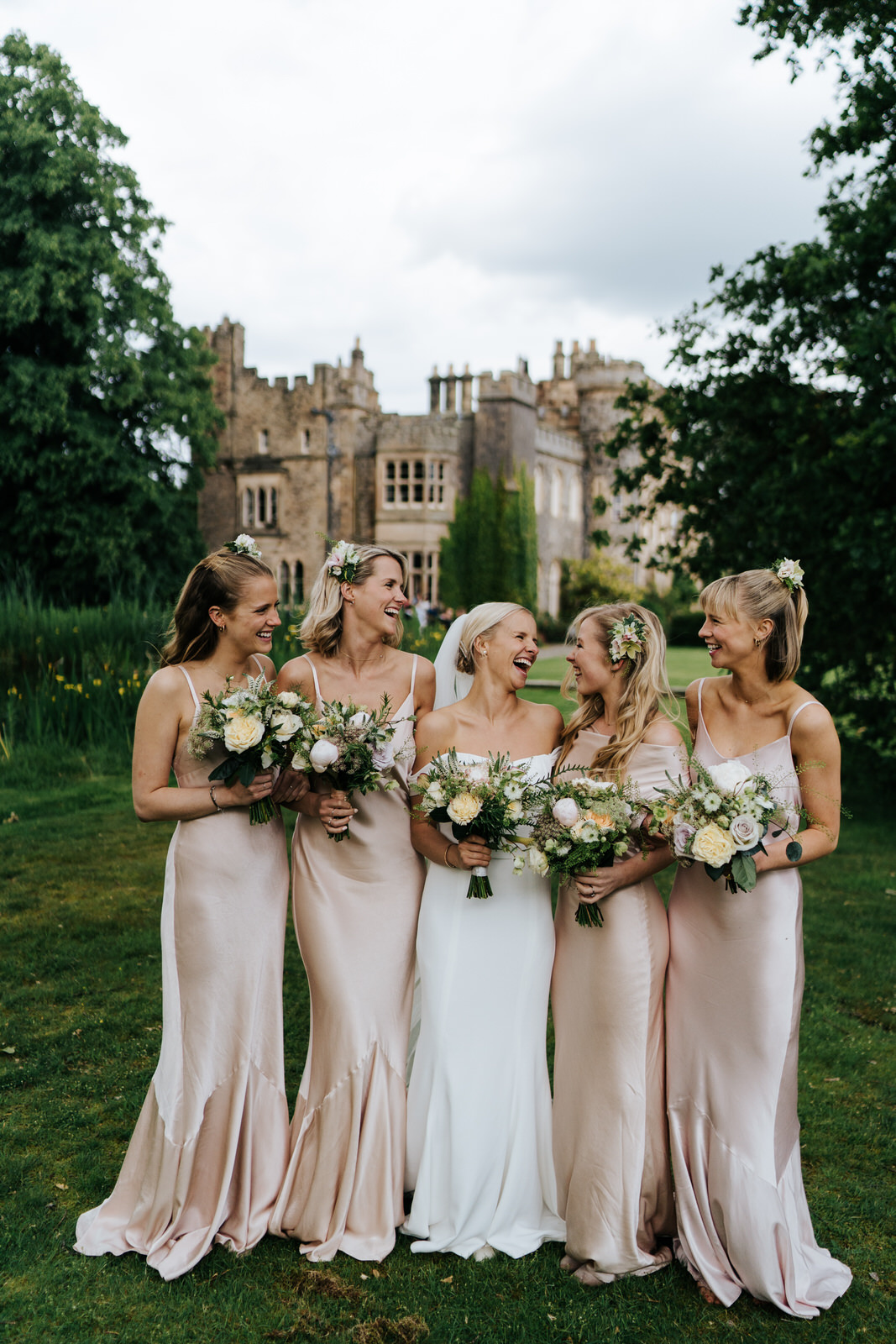 Smiling photograph of bridesmaids and bride holding bouquets with Hawarden Castle in the background