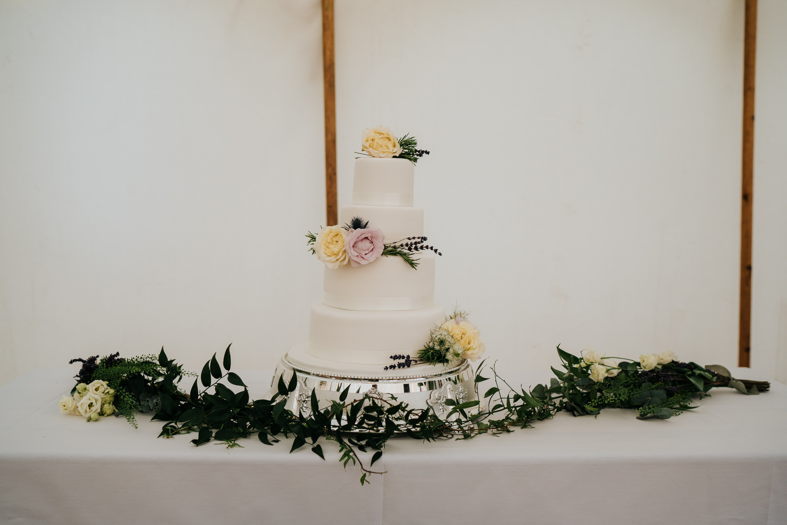 Photograph of three-tiered, white wedding cake with yellow and pink roses as decoration