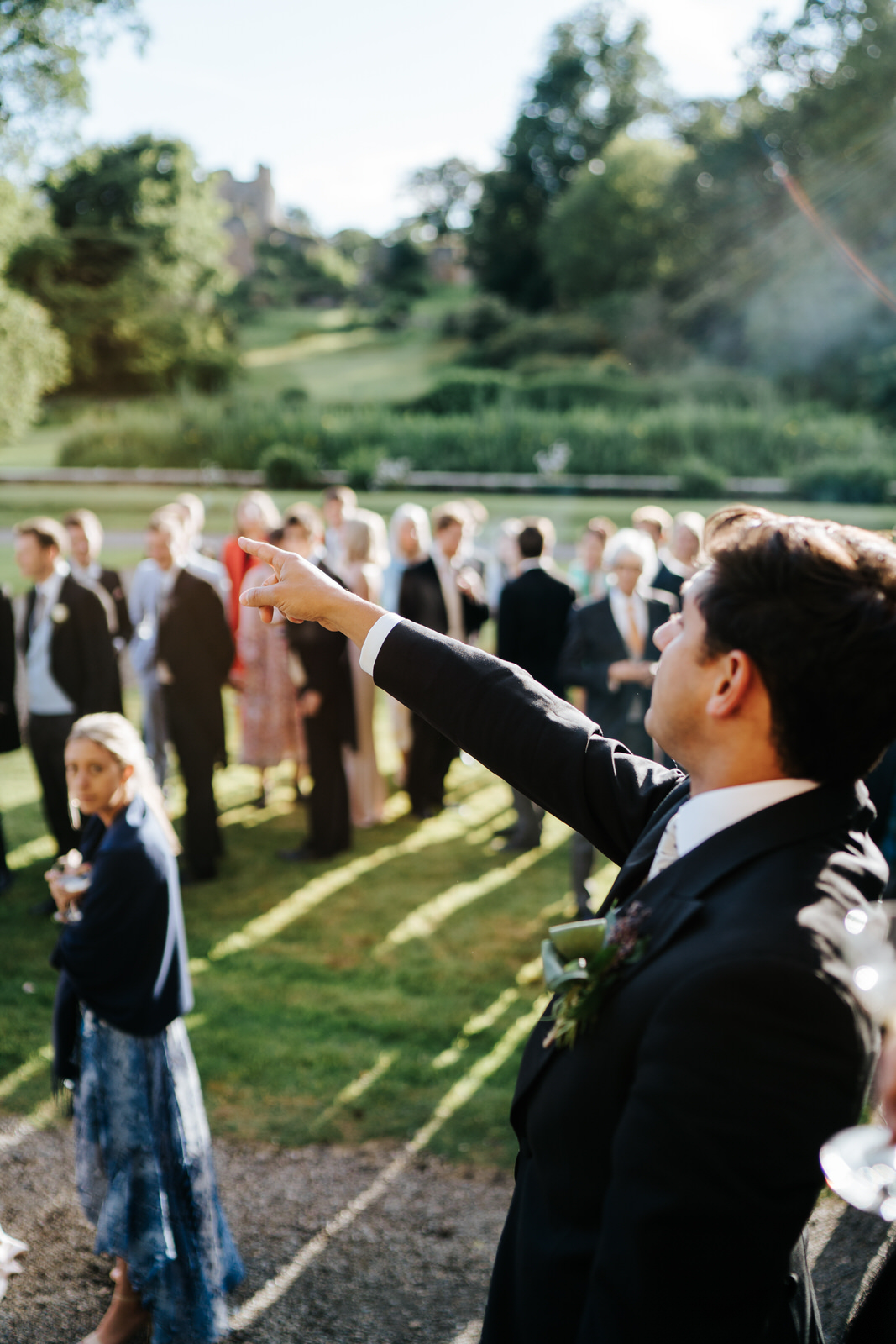 Master of ceremony points towards marquee and instructs guests to make their way towards it
