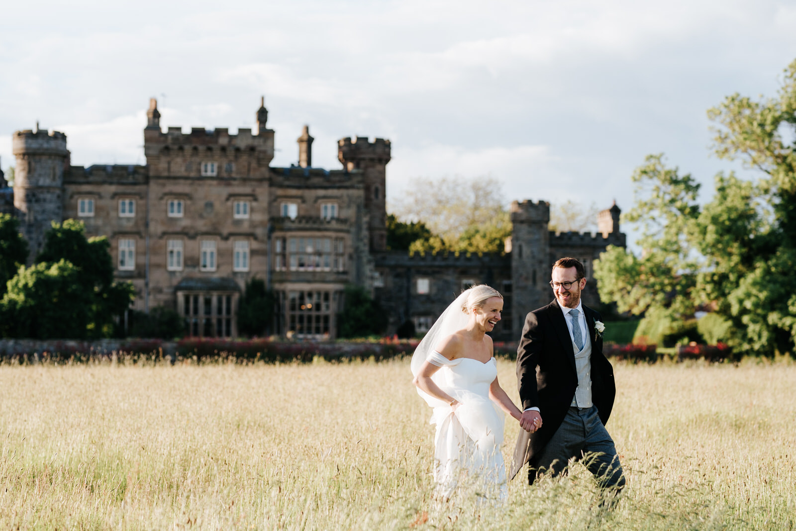 Bride and groom walk through lush fields towards marquee as Hawarden Castle is in the background