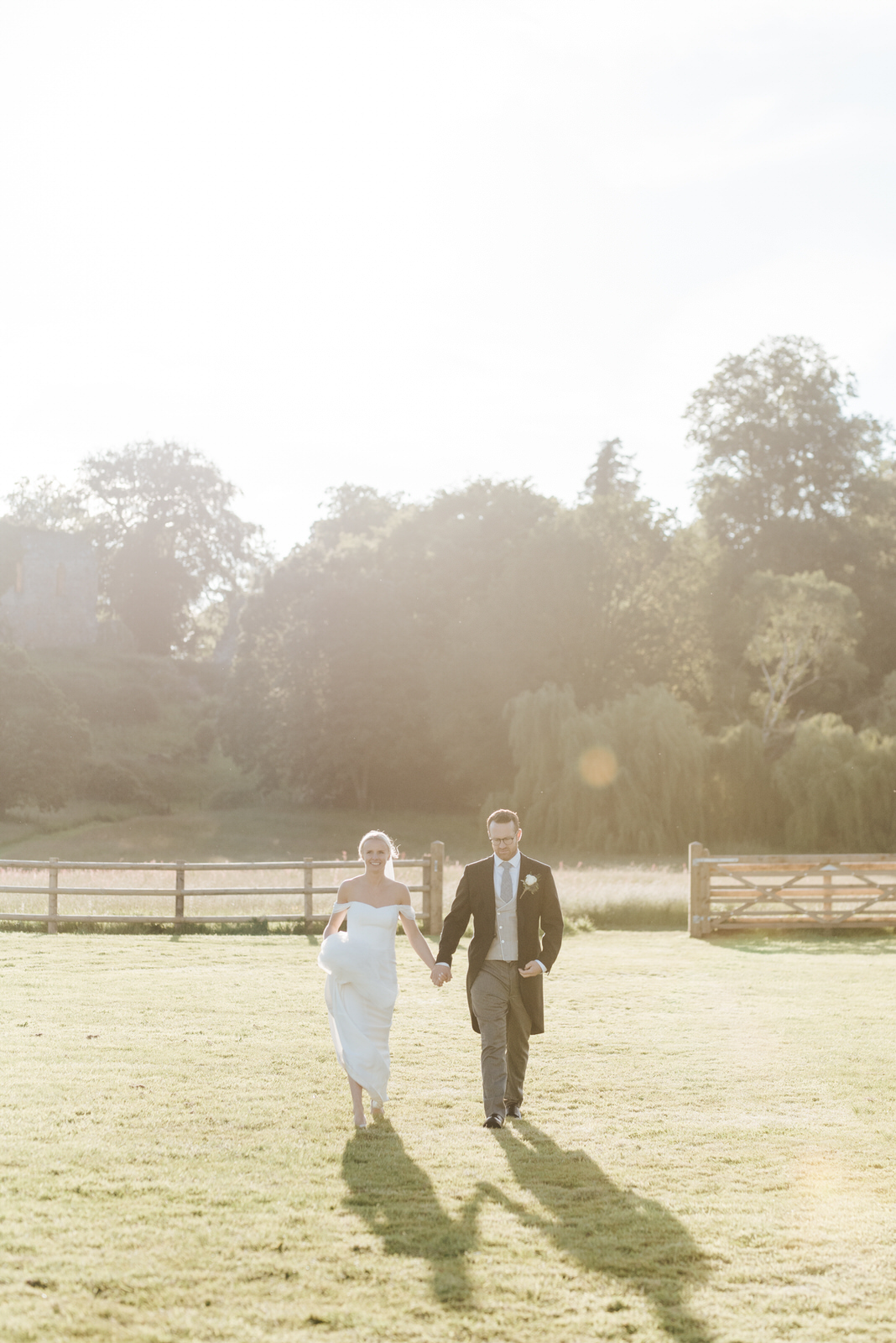 Bride and groom walk towards marquee as sun sets behind them and creates dramatic shadows