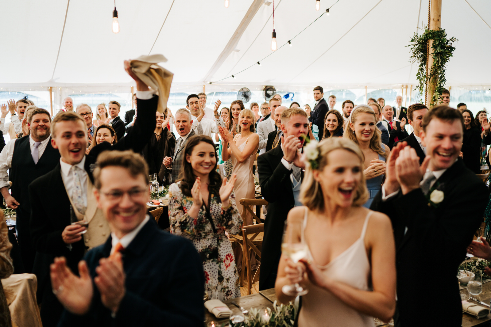 Guests cheer, smile and clap as bride and groom make their way to their table inside wedding marquee