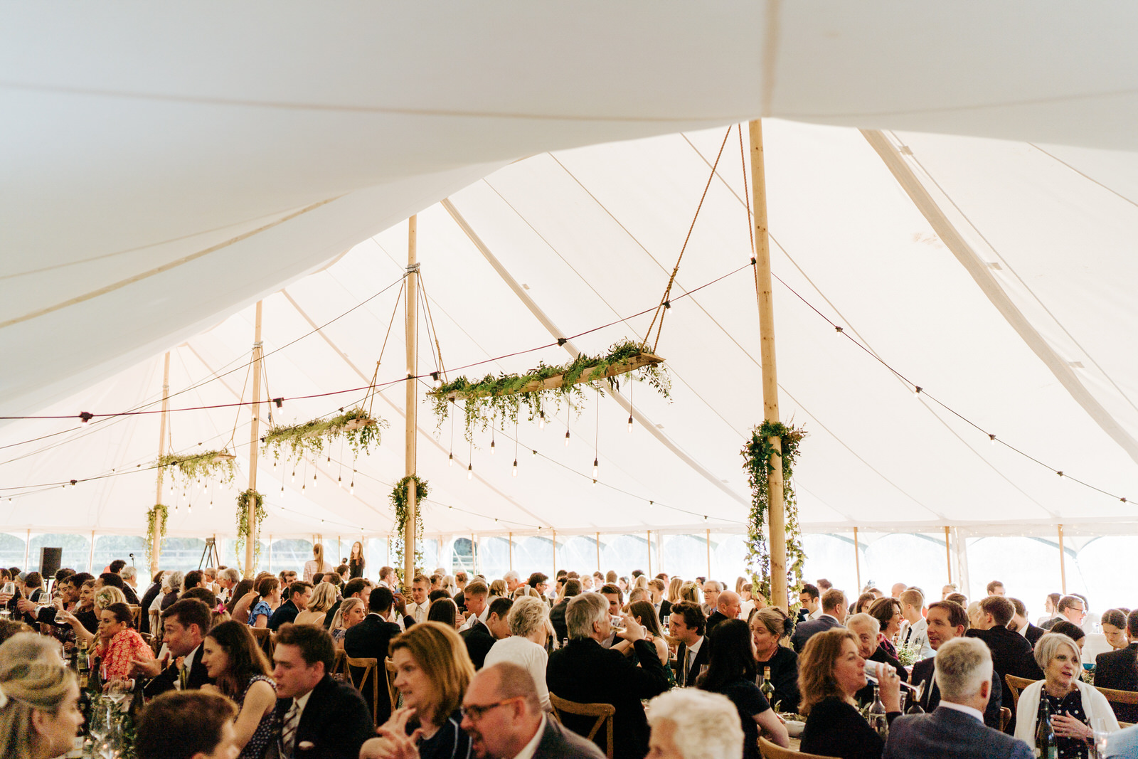 Wide photograph of the entire marquee and all the guests chatting and drinking