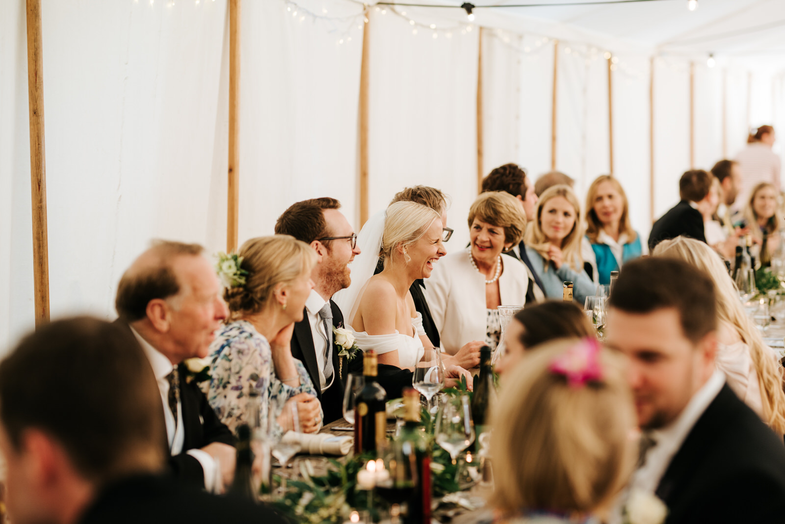 Wide photograph of the head table during the wedding breakfast with bride in the middle, in focus, smiling