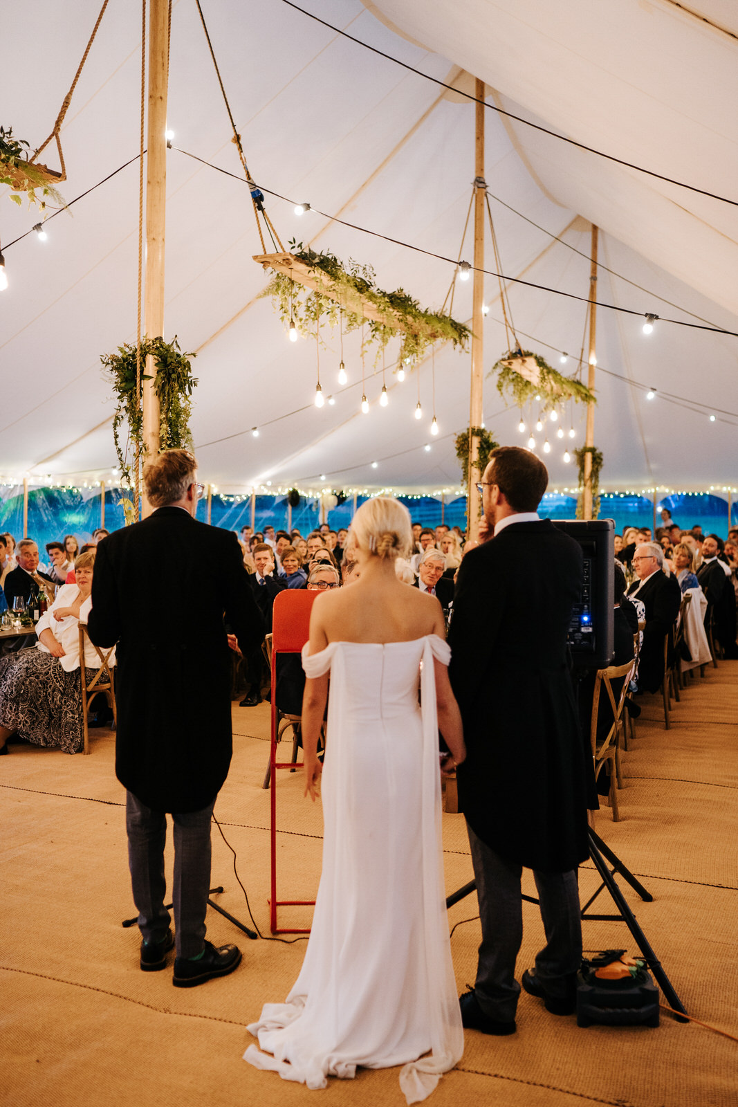 Wide photograph of the father of the bride delivering his speech as guests listen attentively inside marquee at Hawarden Castle, Wales