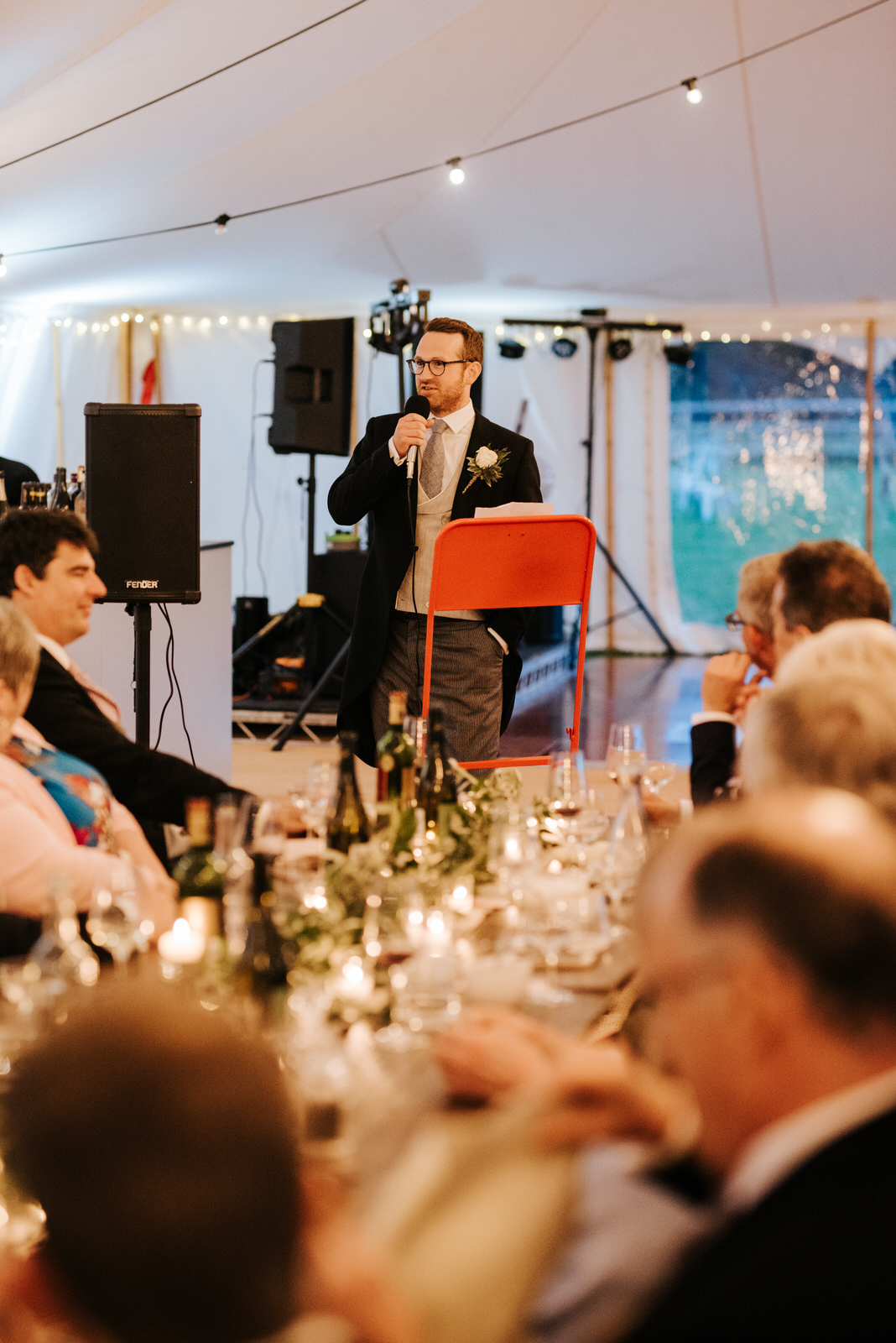 Groom delivers his wedding speech while standing at podium with guests in front