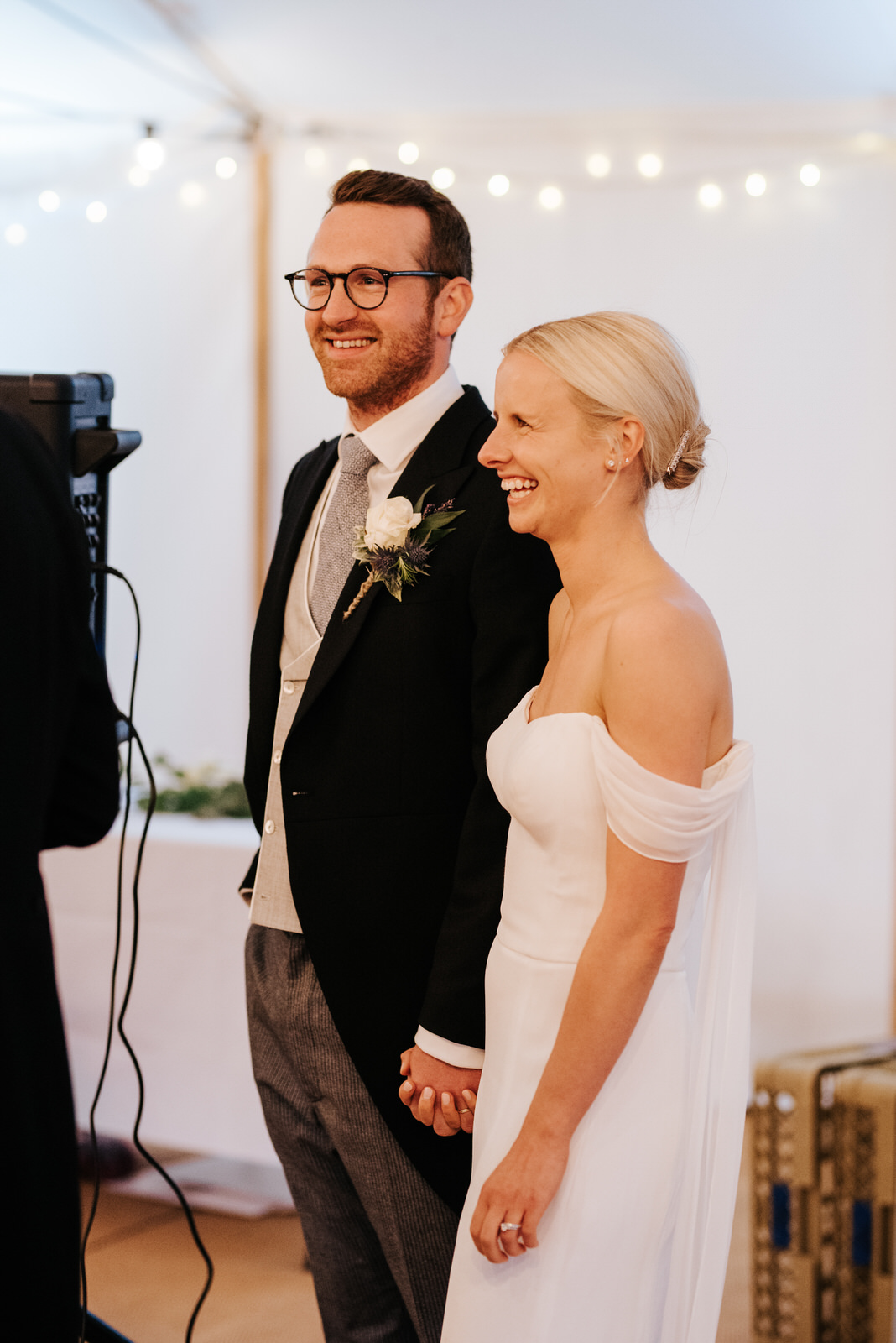 Bride and groom laugh and smile, holding hands, while fathe of the bride delivers wedding speech