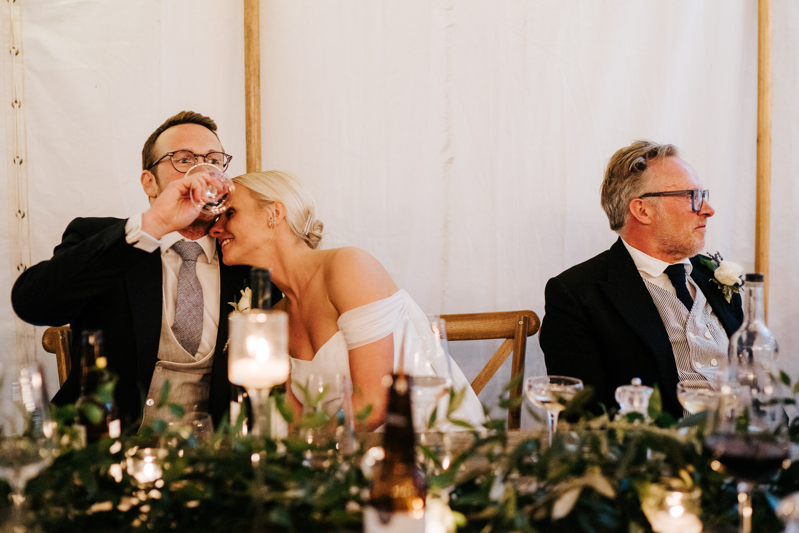 Bride embraces groom, as he takes a drink of wine, after he has completed his speech