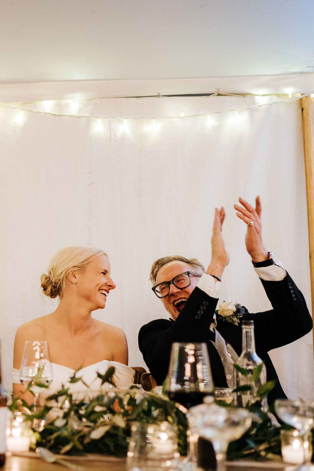 Father of the bride throws his hands into the air and claps while looking at bride, sitting right next to him and smiling