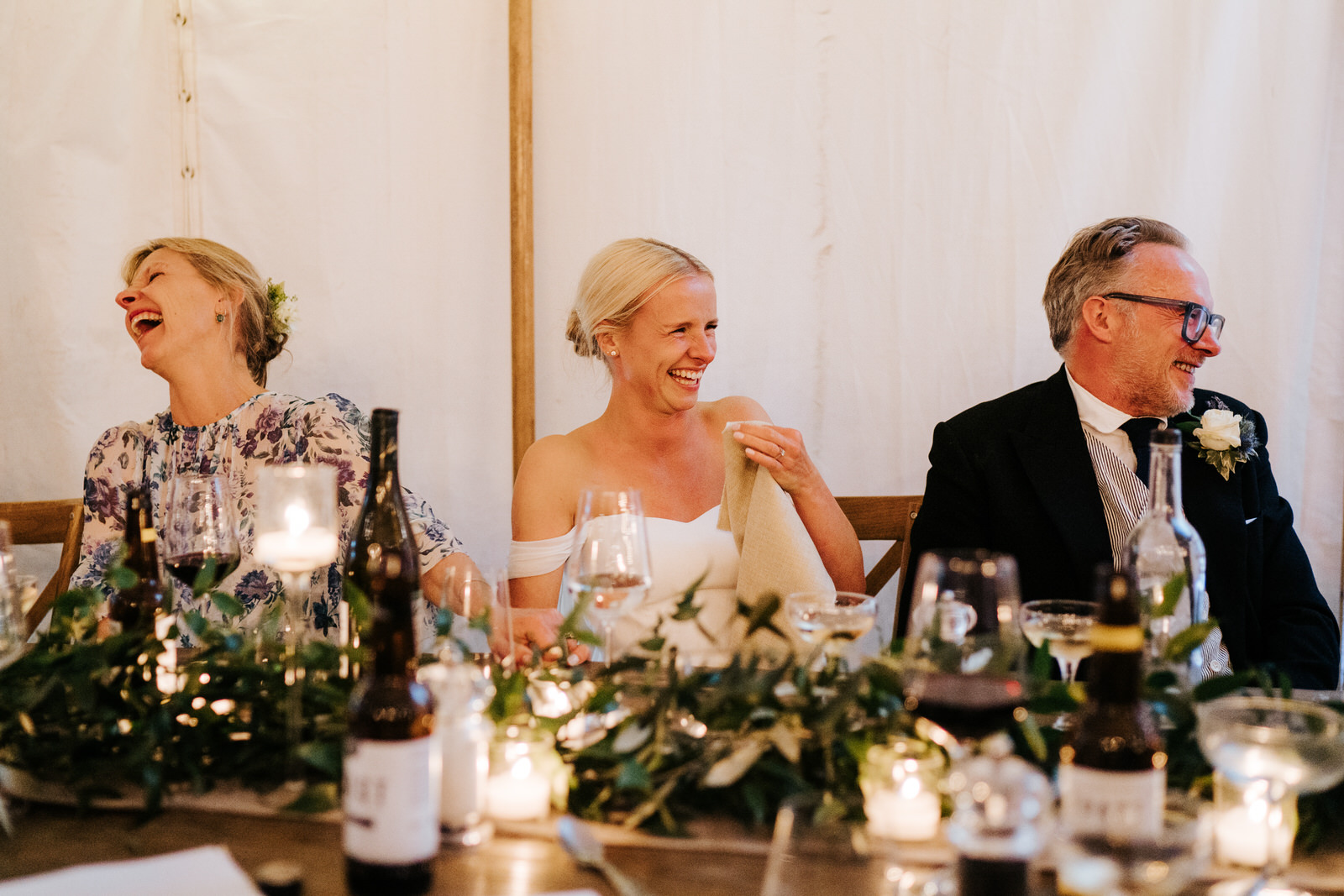 Bride, father of the bride and mother of the bride cannot contain their laughter during the groom's speech
