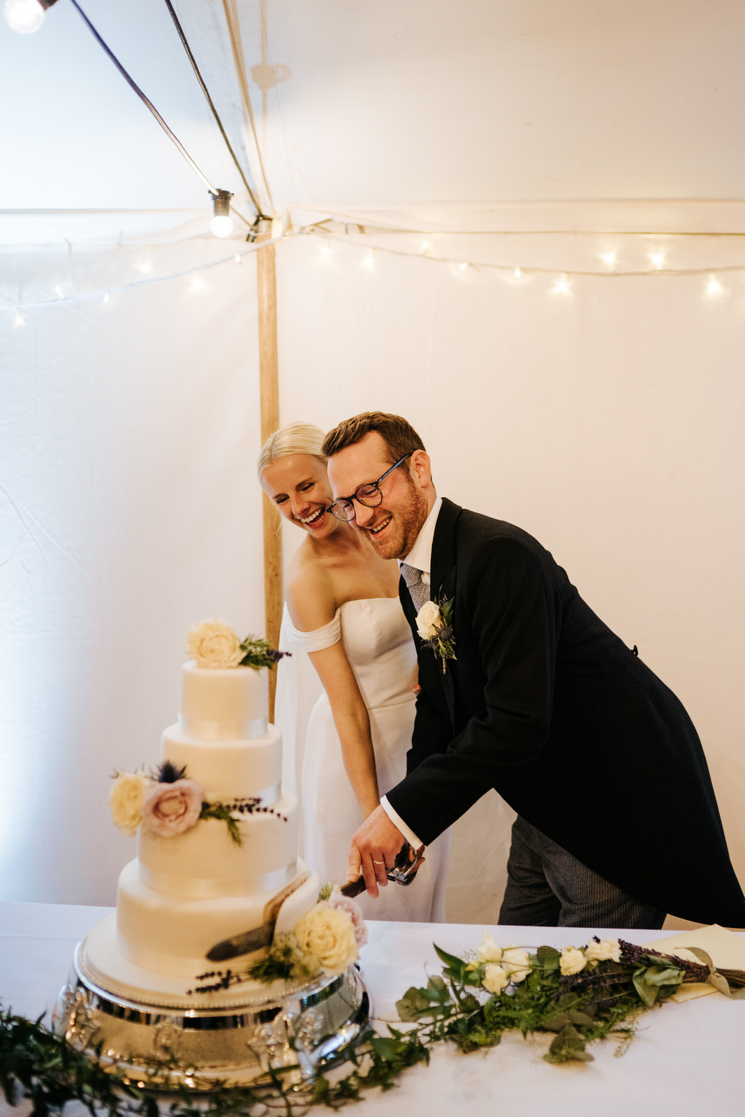 Bride and groom smile as they cut the wedding cake with a sword