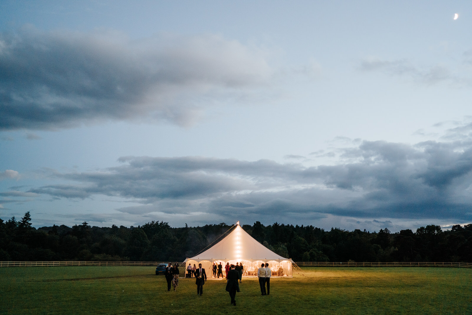 Wide photograph of the marquee during dusk as the moon illuminates the sky at Hawarden Castle in Wales