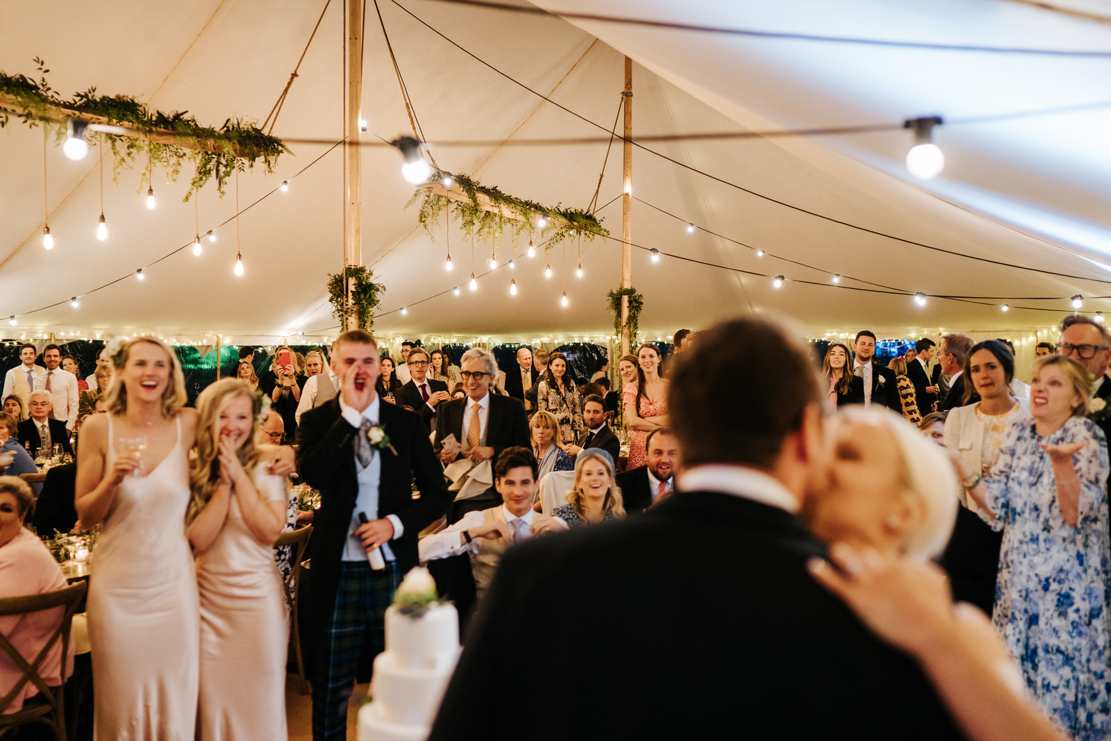 Wide photograph of bride and groom kissing and guests cheering after cutting the wedding cake