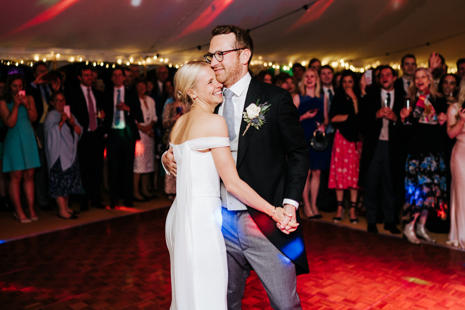 Bride and groom embrace as they have their first dance with guests cheering from the back