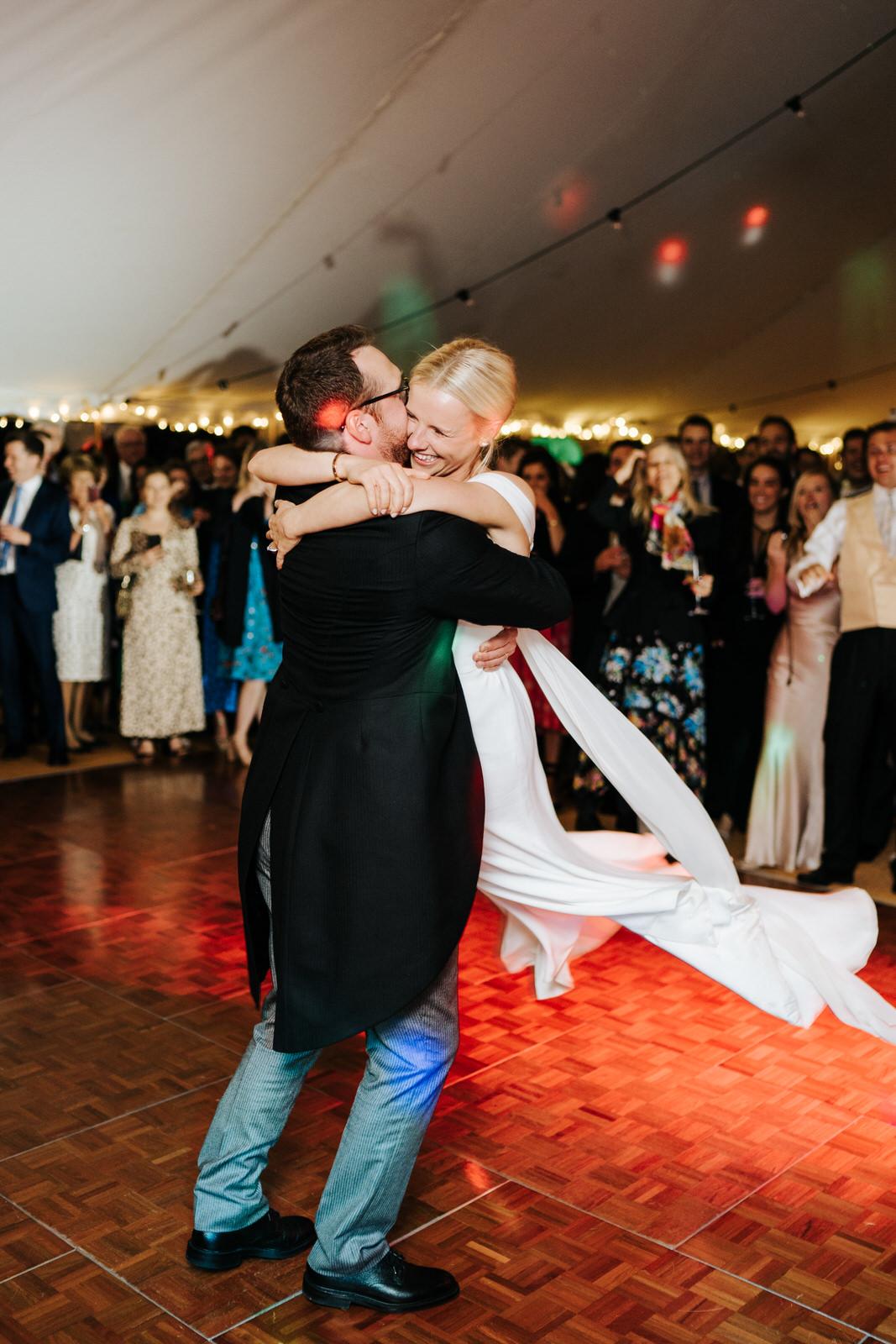 Grooom picks up bride during first dance
