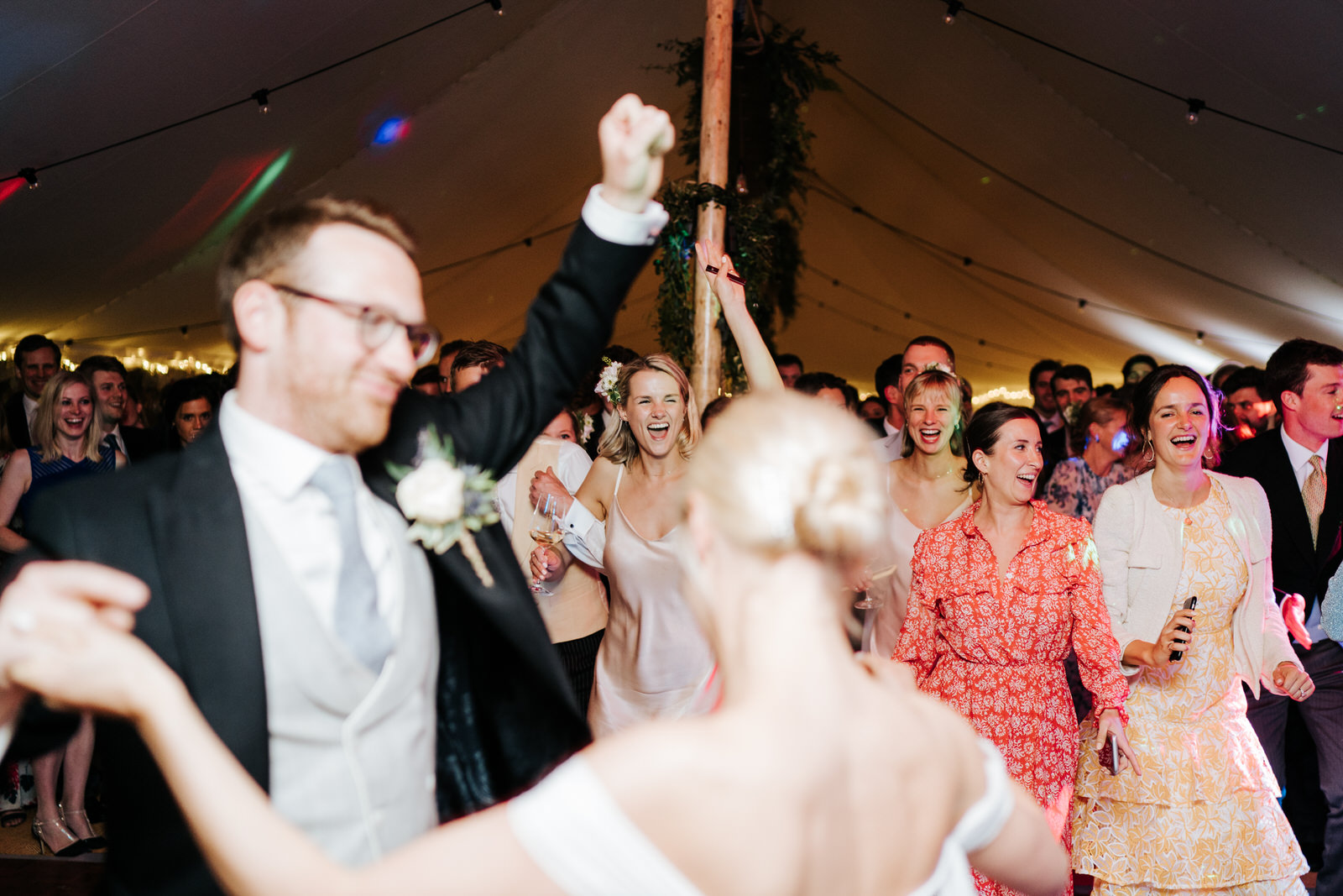 Bride and groom, out of focus in front, finish their first dance and invite guests onto the dancefloor