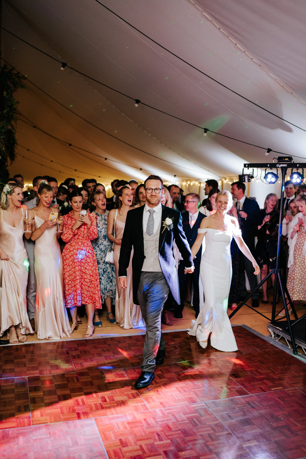 Bride and groom hold hands and walk onto dancefloor to have their first dance