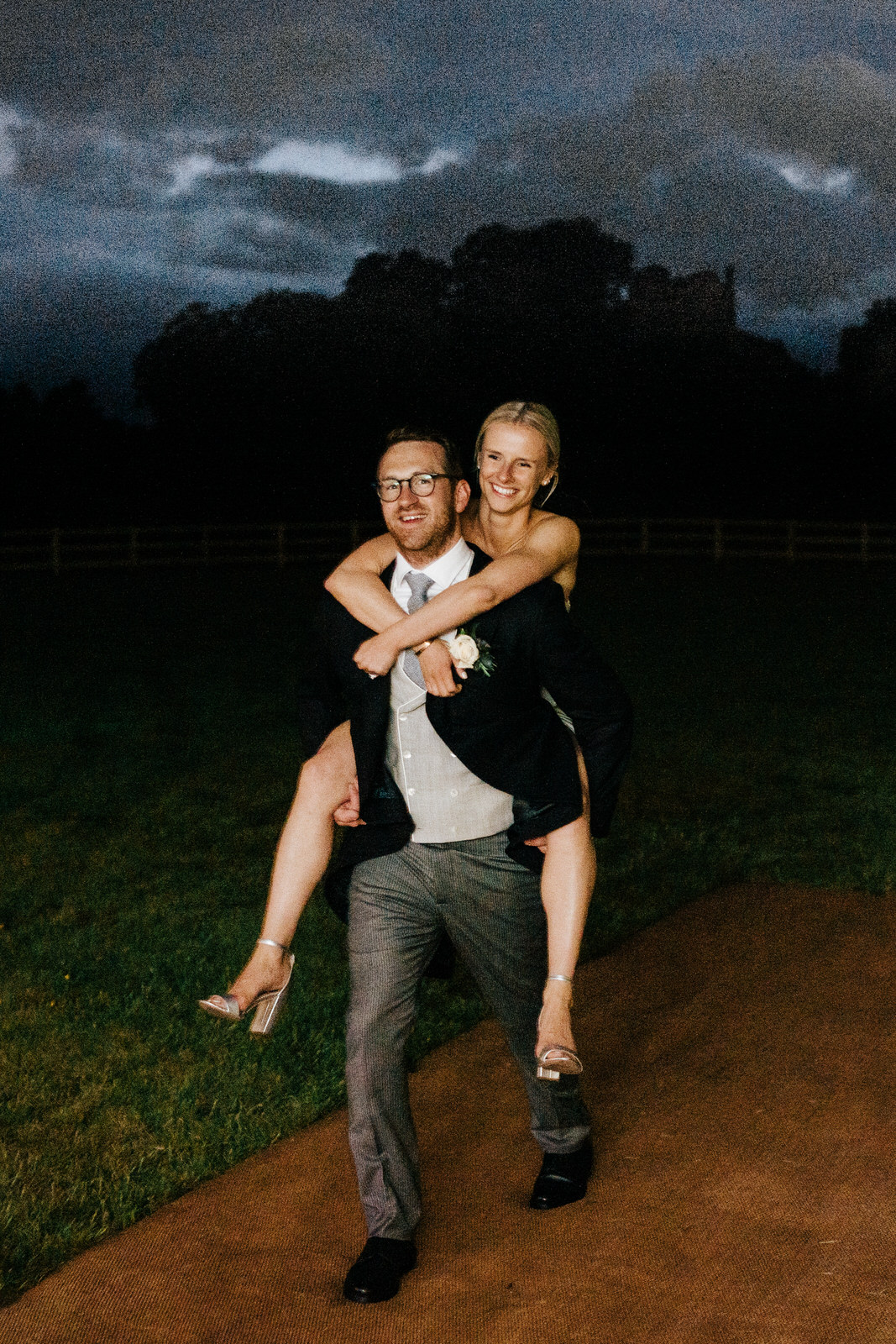 "Bride rides ""piggyback"" style on groom as she re-enters marquee after wardrobe change"