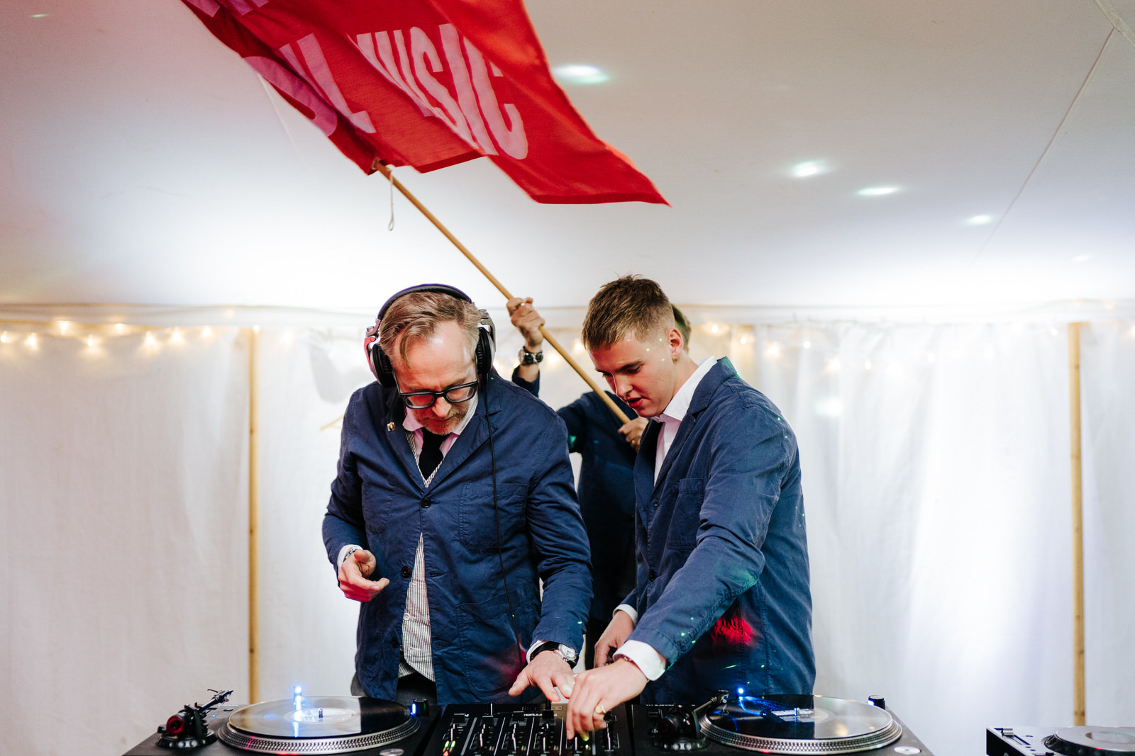 Father of the bride and brothers of the bride DJing behind the decks and waving a big red fan