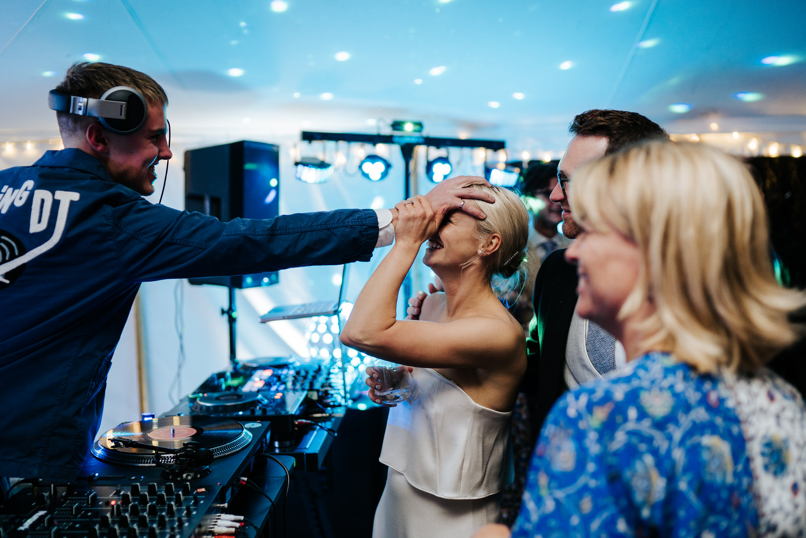 Brother of the bride jokingly grabs bride's head and smiles while doing it