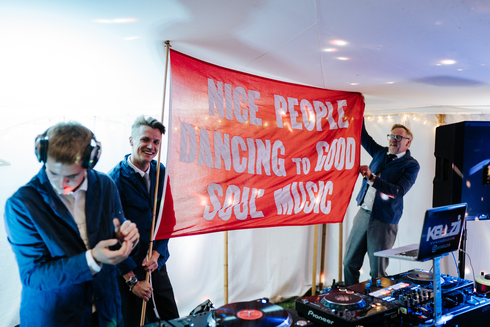 DJs waving big red flag that reads nice people dancing to good soul music