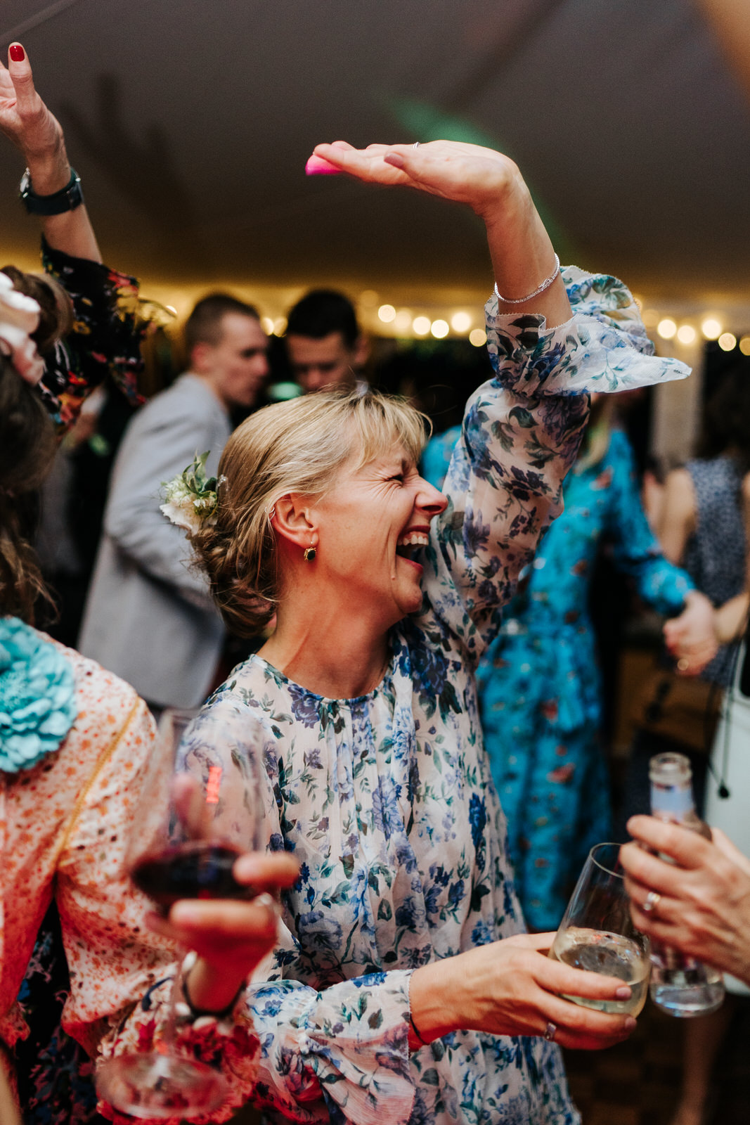 Mother of the bride having the time of her life on the dancefloor smiling and throwing her hand in the air