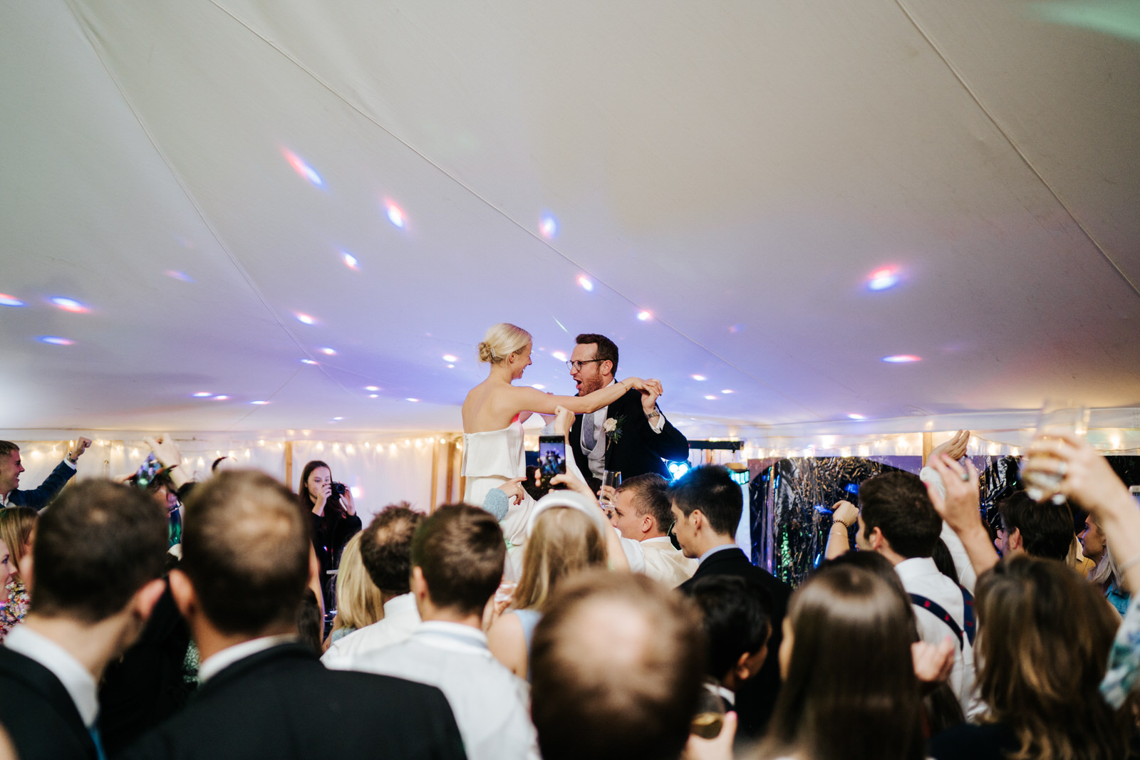 Bride and groom sit on the shoulders of guests while the dancefloor cheers them on