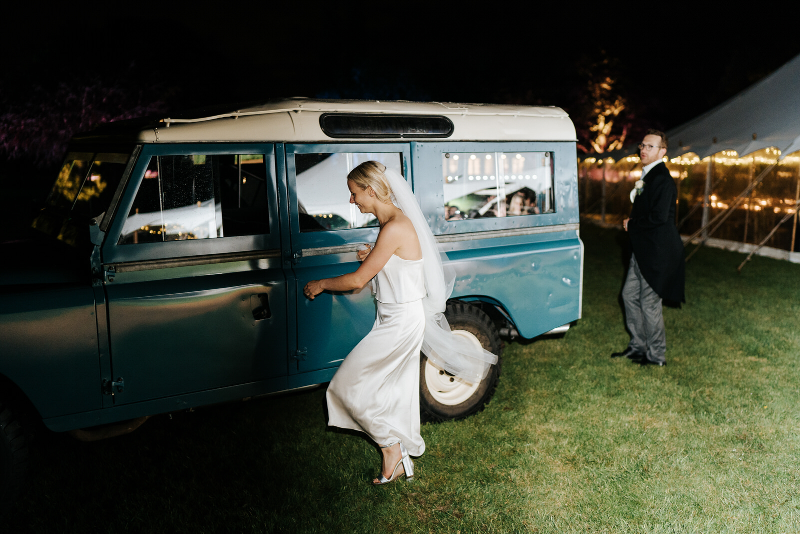 Bride and groom exit marquee and run towards Land Rover to make their wedding exit