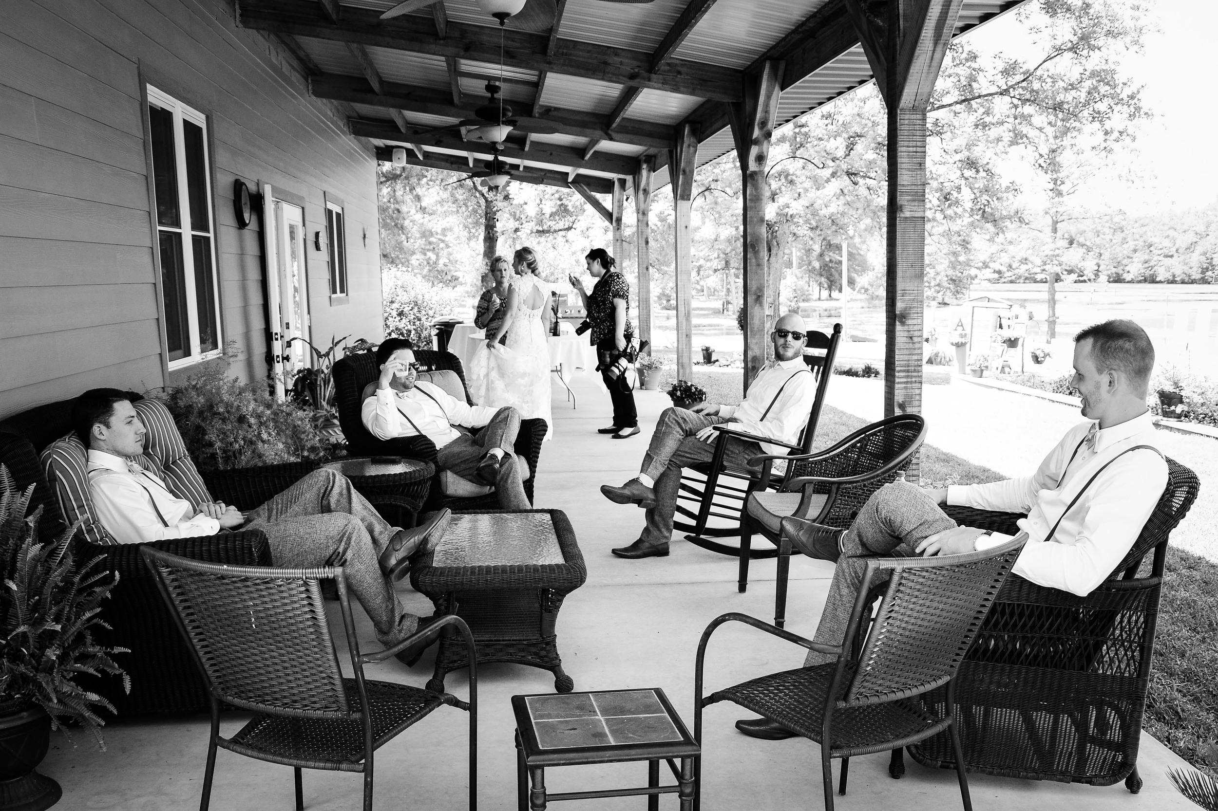 The groomsmen taking some shelter from the sweltering sunand hanging out in the shade.