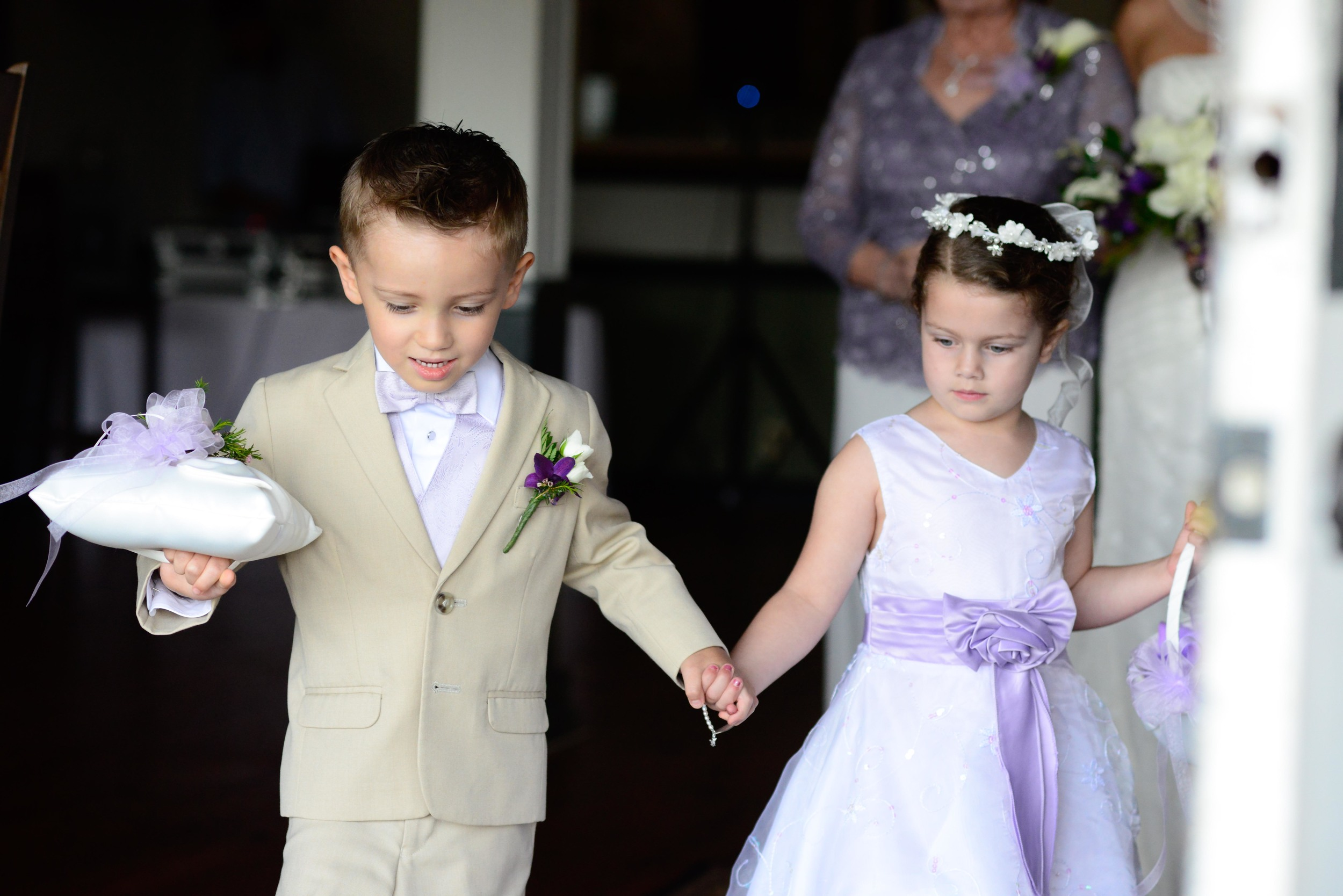 The Flower Girl and Ring bearer in Lilac, White, and Beige.