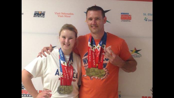 Quincey Epley (c/2019) and her father Matt (c/1995) celebrate success at a power lifting competition. Photo courtesy of Unattached Athlete.