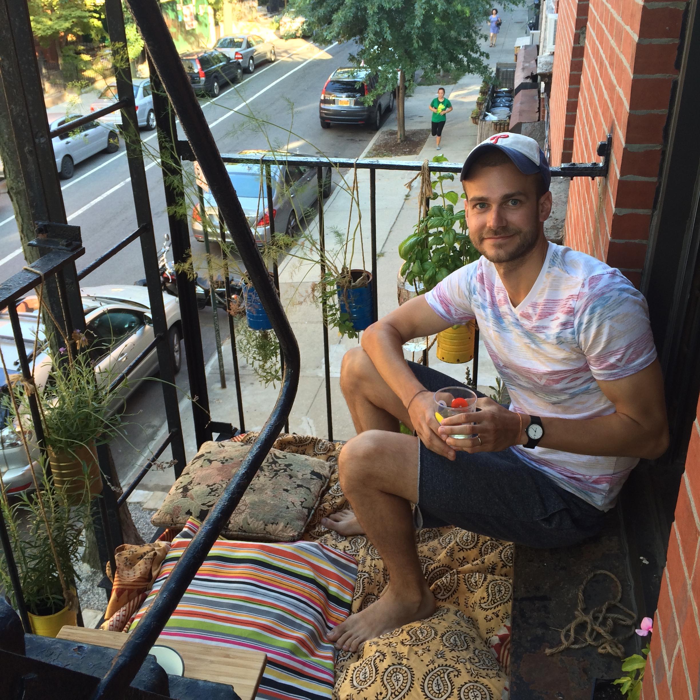 Bri guy on balcony, with wine