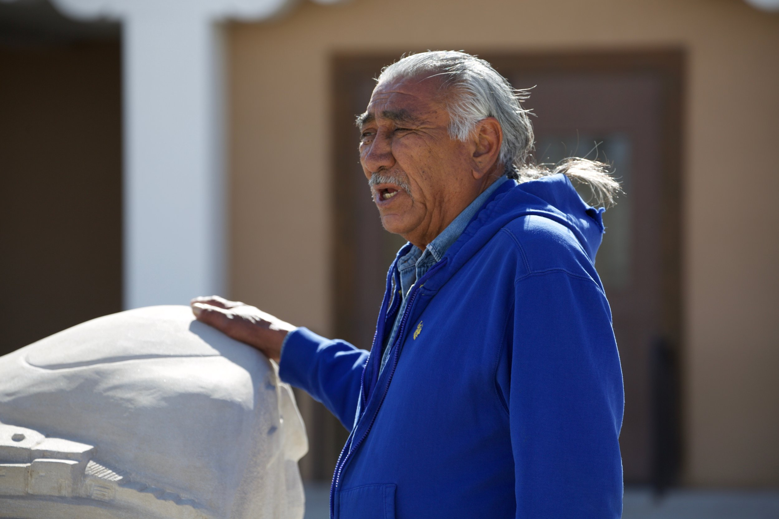 John Suazo explaining the story behind his sculpture at the Taos courthouse.