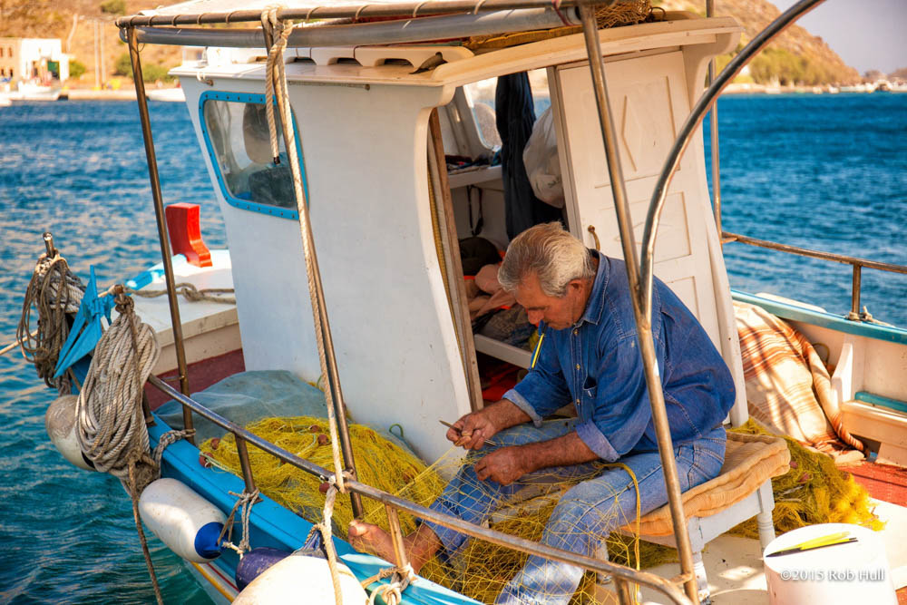 Fisherman in Patmos, Greece, tends to his fishing nets.