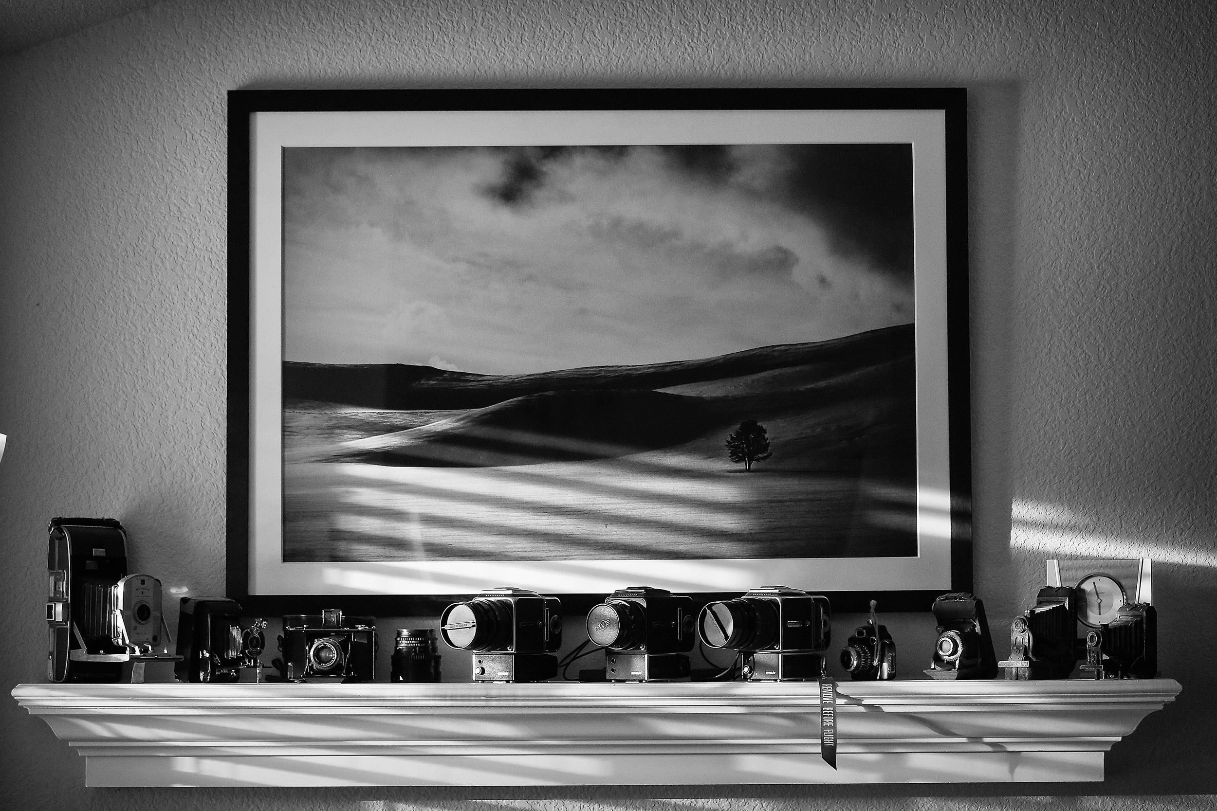 An example where black and white seemed logical since the walls were white, the framed print was b/w and everything in the picture was black. Light and shadow were the primary elements that made this image successful.