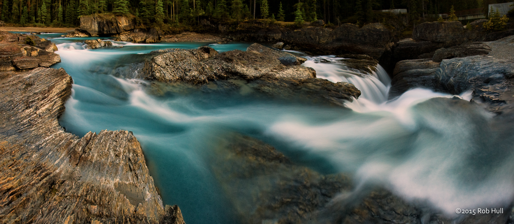 The azure blue water from the Kicking Horse River tumbles down the canyon and undercuts the Natural Bridge rock formation in Canada's Yoho National Park.