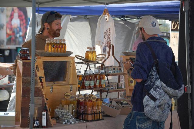 KJ Tencza of Illuman Apiary helping a customer at the Greeley Farmer's Market