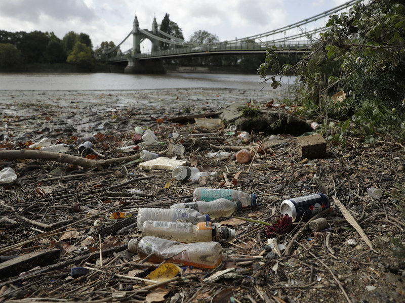 Single-use plastic bottles lie washed up on the bank of the River Thames by the Queen Caroline Draw Dock in London. Image via  Matt Dunham/AP