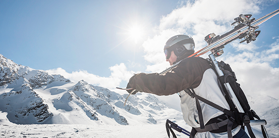 Mid adult male skier walking up mountain with skis, Corvatsch, S