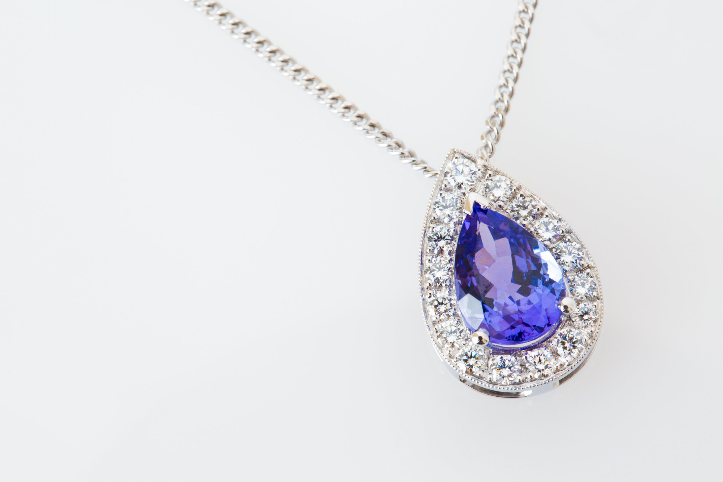 Pendants make a beautiful and thoughtful first anniversary gift, like this magnificent Tanzanite halo piece made for Liz.