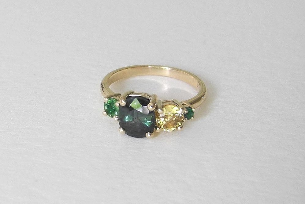 ERICA Engagement Ring:  heirloom blue-green oval sapphire, ethically-sourced emerald, pale yellow sapphire, tsavorite garnet, 14k yellow gold.