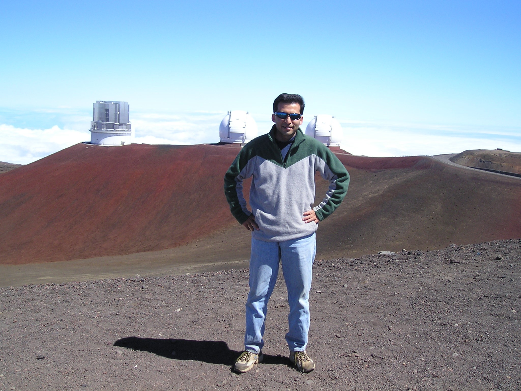 June 2005: In front of the twin Keck Observatories and Subaru Observatory on top of Mauna Kea, Hawaii. Salman was using the James Clark Maxwell Telescope (JCMT) on the summit.