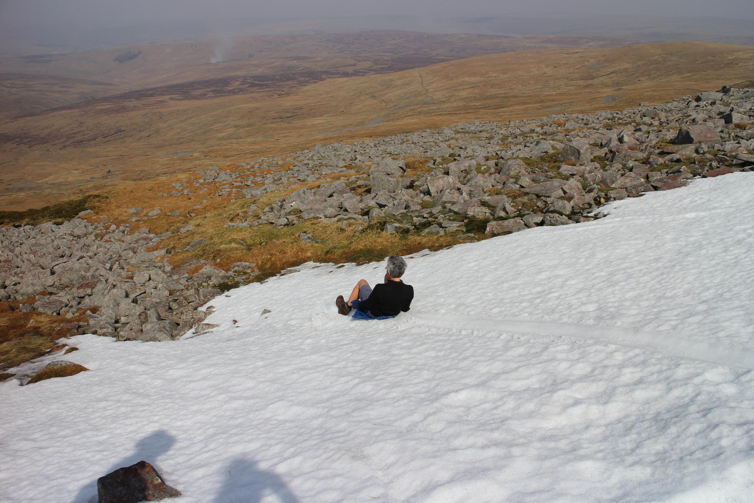 Sue sledding down from Cross Fell