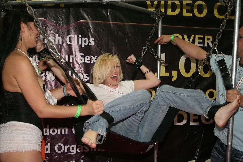 A woman being tickled while restrained and suspended at Exxotica 2009 ©  Stinkie Pinkie