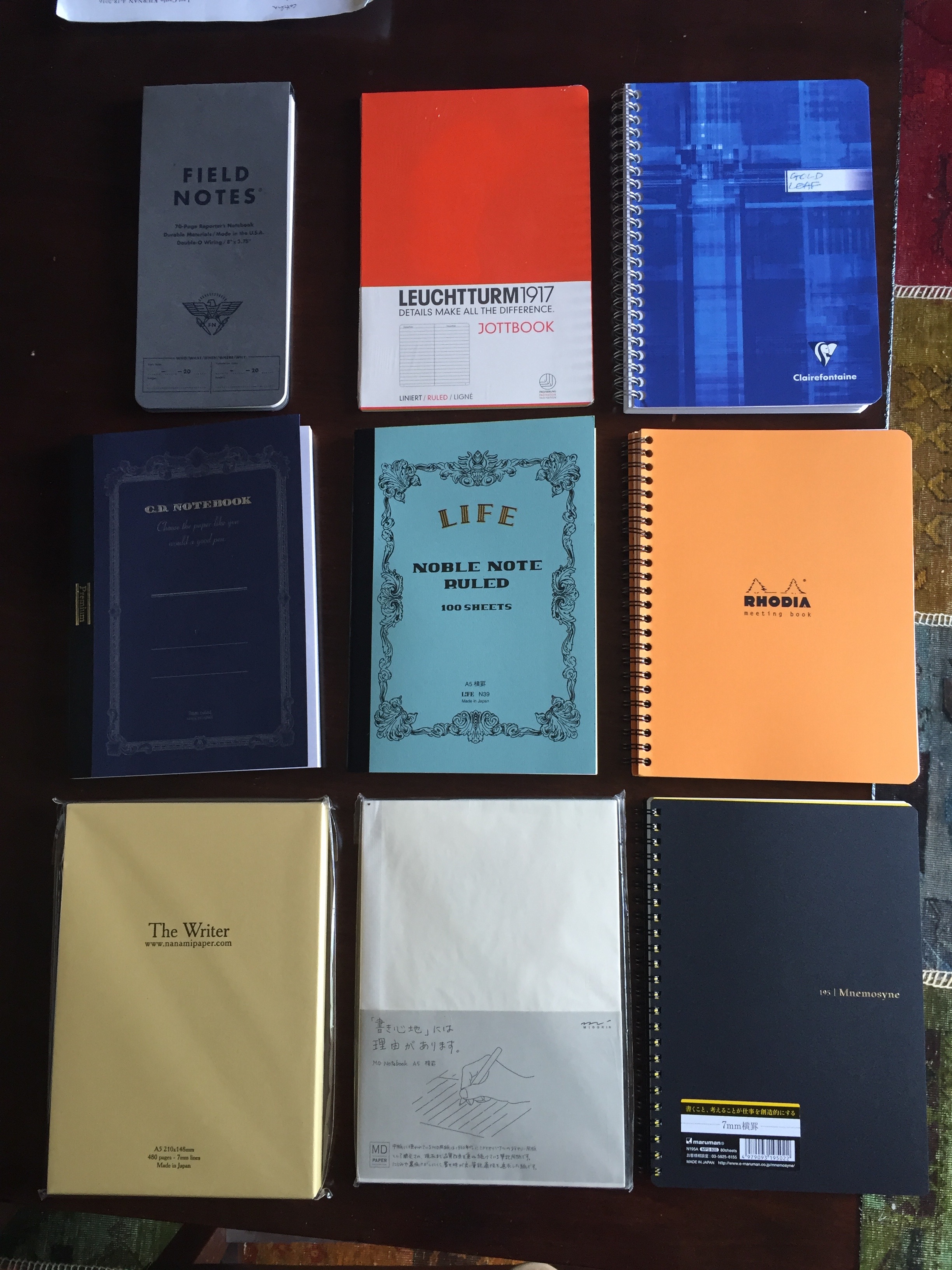 From top, left to right: Field Notes Byline Reporter's Notebook, Leuchtturm 1917 Jottbook, Clairefontaine, Apica CD Notebook, Life Notebook, Rhodia Meeting Book, Nanami Paper's A5 The Writer Notebook, Midori MD Notebook, and the Maruman Mnemosyne 196 A5 Notebook.