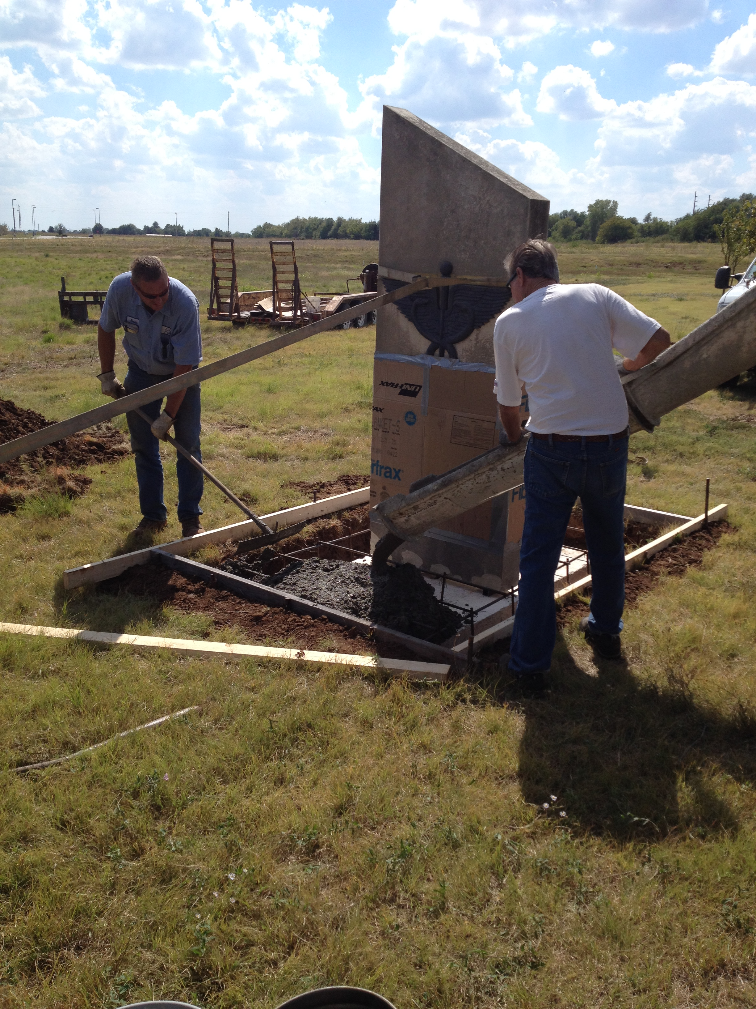 Pictured: Kevin Pike(left) and Rick Crull of LG Pike Construction complete the base for the caduceus stone which was recently relocated from the former site of Memorial Hospital to South Central Kansas Medical Center.