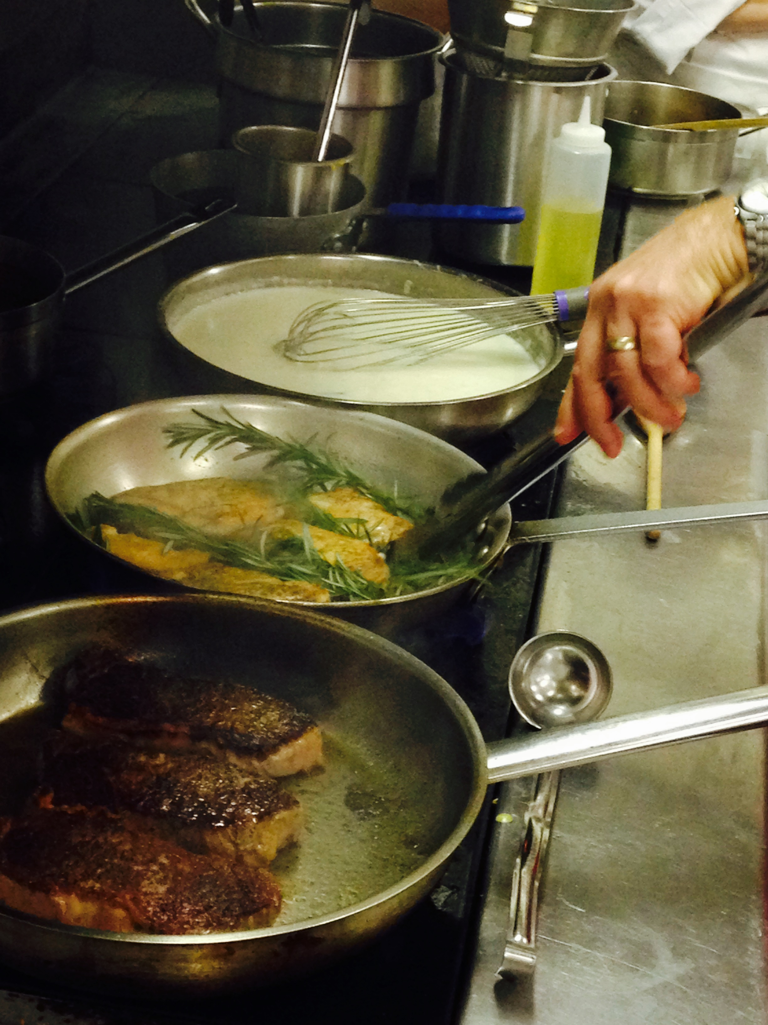 Chef Fournier demonstrated what it's like to cook on the line—managing several hot pans and bubbling stocks at once.